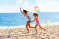 Young girls running with balloons on beach action portrait of colorful Stock Photography