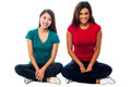 Young girls sitting on the floor studio shot two legs crossed Stock Photos