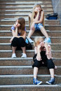 Young girls sitting on a steps Stock Images