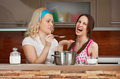 Young girls try soup in the kitchen two Royalty Free Stock Images