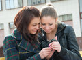 Young girls watch something in mobile phone Royalty Free Stock Images
