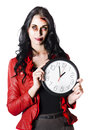 Young glamorous woman in red jacket tired and with head and facial injuries holding a large clock isolated on white background Stock Photos