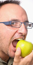 Young with glasses biting apple Royalty Free Stock Photos