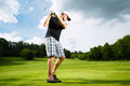 Young golf player on course doing golf swing Royalty Free Stock Photo