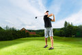 Young golf player on course doing golf swing Royalty Free Stock Photos
