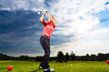 Young golf player on course doing golf swing female she presumably does exercise Stock Photos