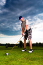 Young golf player on course doing golf swing he presumably does exercise Stock Photography