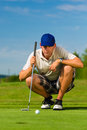 Young golf player on course putting he aiming for his put shot Royalty Free Stock Image
