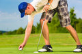 Young golf player on course putting he is at the green Royalty Free Stock Image