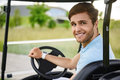 Young golfer driving golf cart Royalty Free Stock Photo