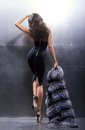 Young and gorgeous actress in a long dress black on metal wall background Stock Photo