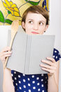 Young gorgeous female cook reading a recipe book with wooden spoon in hand when thinking up cooking ideas Stock Images