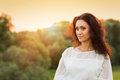 Young gorgeous lady in white dress in sunset beams Royalty Free Stock Photo