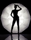 Young gorgeous model posing in studio sexy woman front of giant reflector silhouette shot Royalty Free Stock Image