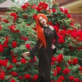 Young gothic girl with red lips in black magnificent dress on dark background. Redhead pale model on background of roses bush. Royalty Free Stock Photo