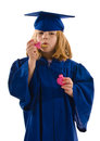 Young graduate her cap gown blowing bubbles dripping bubbles down her graduation gown isolated white vertical layout copy space Royalty Free Stock Photos