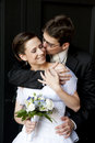 Young groom cuddle beautiful bride and kissing her. Royalty Free Stock Photo
