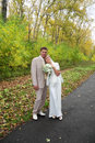 Young groom hugs his bride in autumn park Stock Photography
