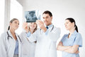 Young group of doctors looking at x ray picture Stock Photos