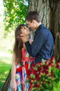 Young guy affectionately hugs girl in a sunny nature Royalty Free Stock Image