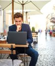 Young guy business man with laptop at table of summer cafe on street working outdoors