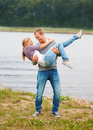 Young guy carrying his girlfriend in his arms Stock Images