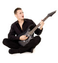 A young guy dressed in black clothes sits and plays the guitar Royalty Free Stock Photo