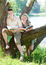The young guy and the girl read books on the lake Stock Photo