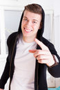 Young guy with great smile in active sportswear hood pointing cool finger at camera Royalty Free Stock Photography