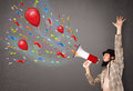 Young guy having fun shouting into megaphone with balloons and confetti Stock Images