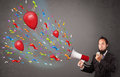 Young guy having fun shouting into megaphone with balloons and confetti Royalty Free Stock Photos