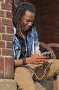 Young guy listening to music black man on his smart phone Royalty Free Stock Photography