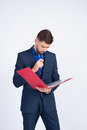 Young guy looks in the red folder studio picture a man a blue suit Royalty Free Stock Photos