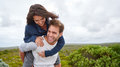 Young guy piggybacking his girlfriend outdoors laughing giving a piggyback while on a nature trail Stock Image