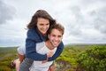 Young guy playfully piggybacking his girlfriend outdoors smiling having fun in nature and Royalty Free Stock Photos