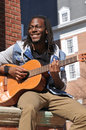 Young guy playing guitar in the city happy black man Royalty Free Stock Image