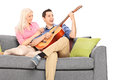 Young guy playing guitar with his girlfriend confident seated on sofa isolated on white background Stock Images