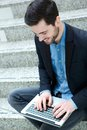 Young guy smiling and using laptop portrait of a Royalty Free Stock Photo