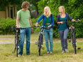 Young guys and girls with bicycle in the nature fi Royalty Free Stock Photography