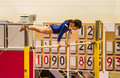 Young gymnast girl performing routine on high bar a choreographed horizontal while practicing for the competition with score table Royalty Free Stock Photo