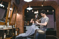 Young hairdresser drying man's hair with blowdryer Royalty Free Stock Photo