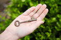 Young hand holding antique key Royalty Free Stock Photo