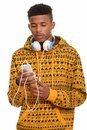 Young handsome African man using mobile phone while wearing head Royalty Free Stock Photo