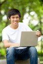 Young handsome Asian student with laptop Stock Photo