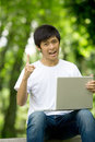 Young handsome Asian student with laptop Royalty Free Stock Images