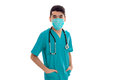Young handsome brunette man doctor in uniform and mask with stethoscope on his shoulders looking at the camera isolated Royalty Free Stock Photo