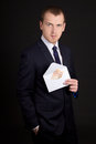 Young handsome business man holding envelope with money euro banknotes Stock Photos