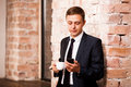 Young handsome businessman in black suit is drinking coffee and surfing in the phone near brick wall Royalty Free Stock Photo
