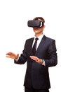 Young handsome businessman in black suit wearing virtual reality goggles., isolated on white background Royalty Free Stock Photo