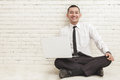 Young handsome businessman with laptop smiling and sitting on th Royalty Free Stock Photo
